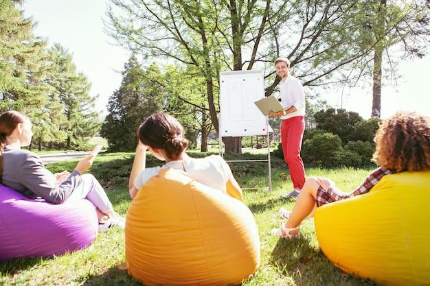 Beste studenten. vrolijke jongeman permanent in de buurt van het bord en hun universitaire project bespreken met zijn vrienden