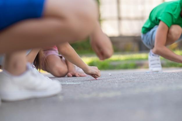 Beste tijd. betrokken geïnteresseerde kinderen tekenen met kleurpotloden op asfalt in park op zomerdag, geen gezicht