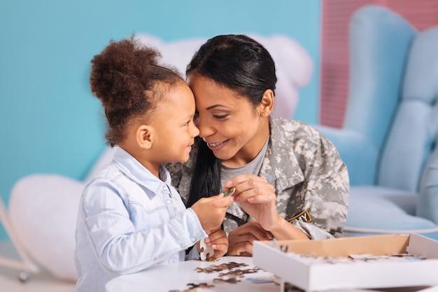 Beste tijd. leuke liefdevolle geweldige moeder en dochter die een schattig moment delen terwijl ze aan de witte tafel zitten en een puzzel voltooien