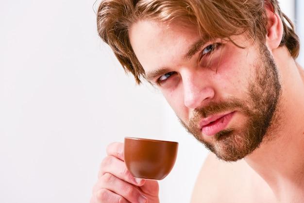 Beste tijd om je kopje koffie te drinken. guy aantrekkelijk uiterlijk man geniet van warme vers gezette koffie close-up. eerste slok. elke ochtend met zijn koffie. man bebaarde knappe macho houdt kopje koffie.