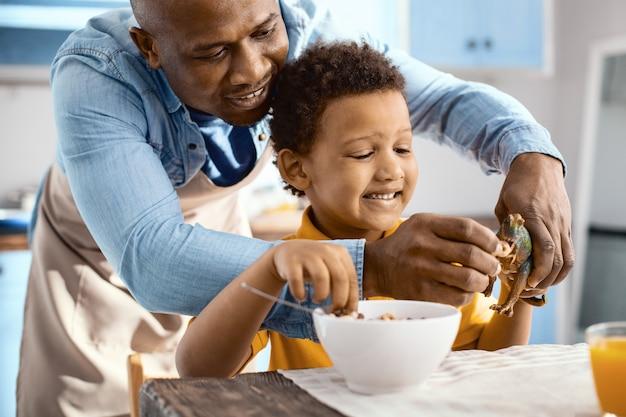 Beste tijdverdrijf. gelukkige jonge vader die granen voedt met de speelgoeddinosaurus van zijn zoon en gelukkig lacht terwijl de jongen aan het ontbijt