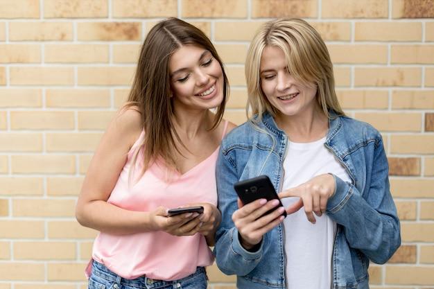 Beste vrienden die buiten op hun mobiele telefoon kijken
