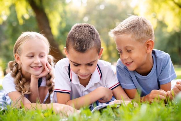 Beste vrienden die een boek op een picknickdeken lezen