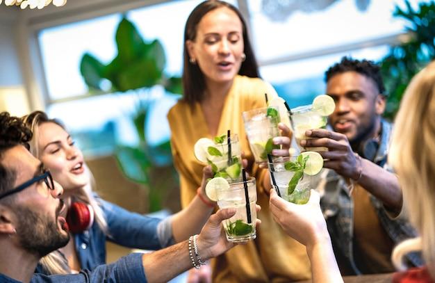 Beste vrienden die mojito drinken in een mode-cocktailbar-restaurant - vriendschapsconcept met jonge mensen die plezier hebben met het roosteren van drankjes op happy hour in de pub - focus op rechts glas - levendig neonfilter
