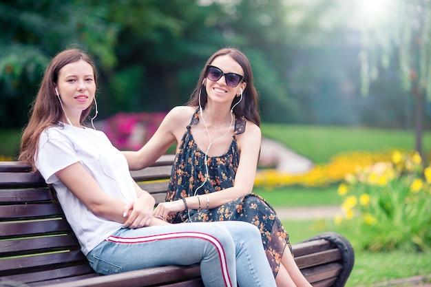 Beste vrienden die op een bank in een de zomerpark zitten