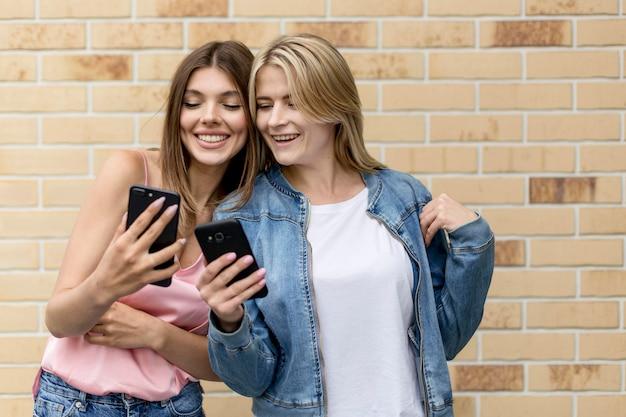 Beste vrienden die op hun mobiele telefoons kijken
