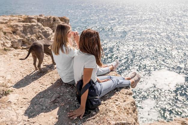 Beste vrienden die op rotsen naast de oceaan zitten