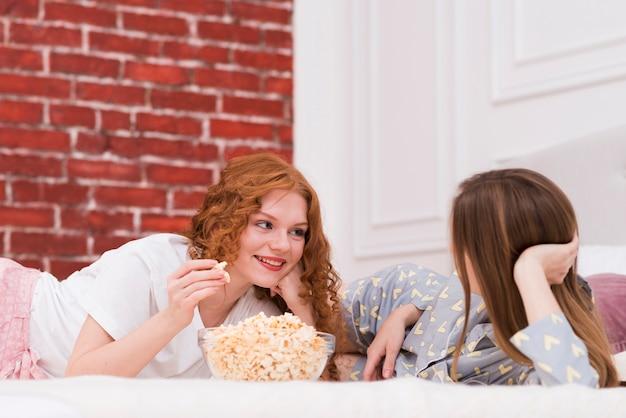 Beste vrienden die popcorn eten terwijl in bed