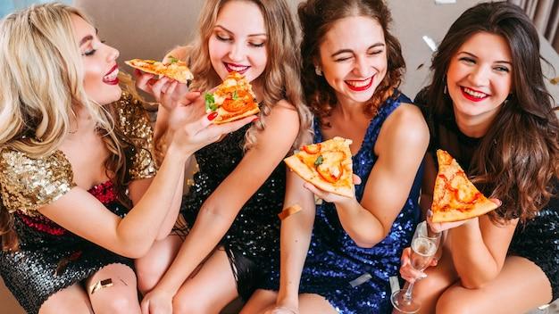 Beste vrienden die rondhangen, plezier maken, lachen. jonge dames die elkaar voeden met heerlijke pizza.
