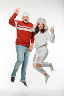 Beste vrienden die samen springen terwijl ze winterkleren dragen