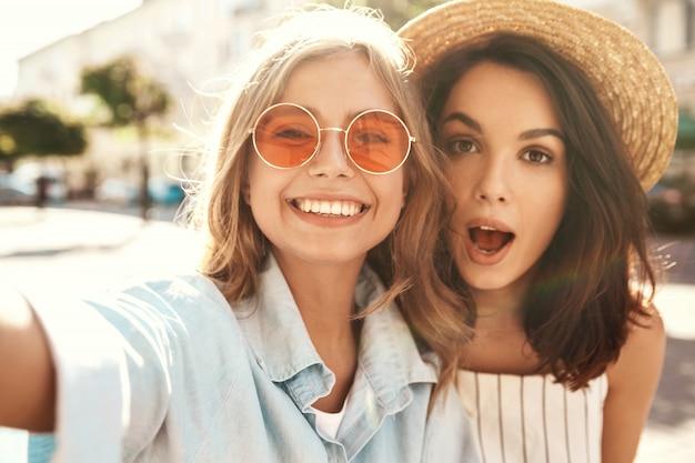 Beste vrienden dragen een stijlvolle outfit en nemen selfie op straat