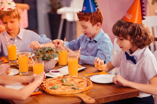 Beste vrienden. ernstige jongen met krullend haar aan de tafel zitten tijdens het eten van pizza