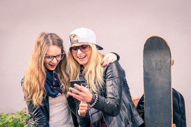 Beste vrienden genieten van tijd samen buitenshuis met smartphone