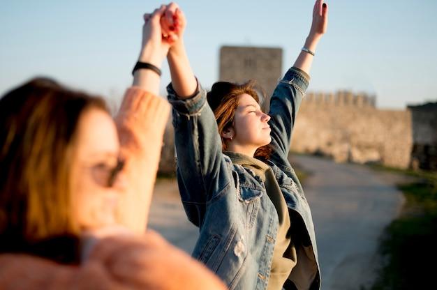 Beste vrienden houden hun handen in de lucht zijwaarts uitzicht