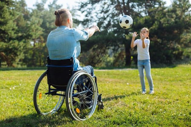 Beste vrienden. jonge man met een handicap zittend in een rolstoel en volleyballen met zijn schattige dochtertje tijdens hun wandeling in het park