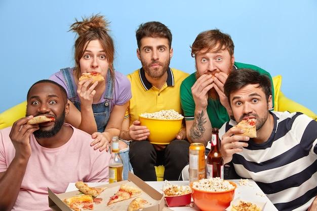 Beste vrienden kijken thuis tv, genieten van hun vrije dag, eten lekkere pizza en popcorn