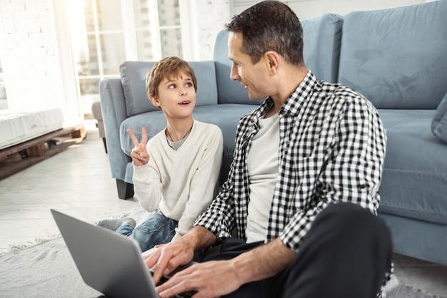 Beste vrienden. knappe waakzame blonde jongen glimlachend en zittend op de vloer met zijn vader en zijn vader met een laptop en ze kijken elkaar aan