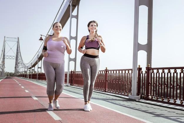 Beste vrienden. leuke positieve vrouwen die lachten tijdens het samen joggen op de brug