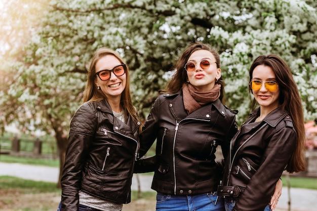 Beste vrienden meisjes plezier, vreugde. levensstijl. mooie jonge vrouwen in zonnebril gekleed in de mooie kleren glimlachend op een zonnige dag. foto's van meisjes door bloeiende bomen