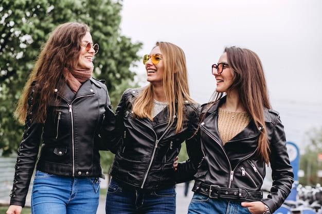 Beste vrienden meisjes plezier, vreugde. levensstijl. mooie jonge vrouwen in zonnebril gekleed in de mooie kleren glimlachend op een zonnige dag. foto's van meisjes tegen de achtergrond van bloeiende bomen