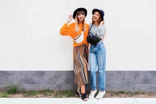 Beste vrienden omarmen, paar stijlvolle meisjes poseren op wit