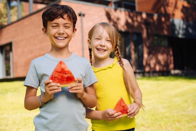 Beste vrienden ooit. alert charmante kinderen glimlachen en eten van een rijpe watermeloen