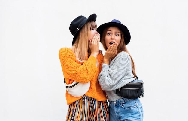 Beste vrienden, paar stijlvolle meisjes poseren op wit