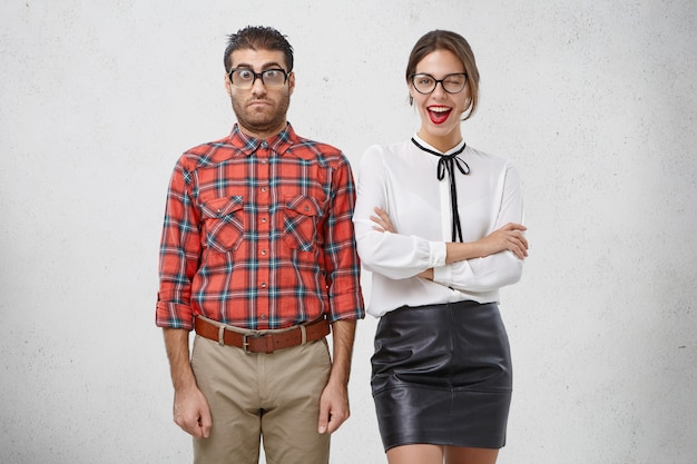 Beste vrienden staan naast elkaar: ongeschoren verbaasde man in bril en geruit overhemd en mooie vrouw knipoogt vreugdevol met oog