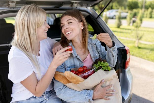 Beste vrienden zittend op een kofferbak terwijl ze een boodschappentas vasthouden