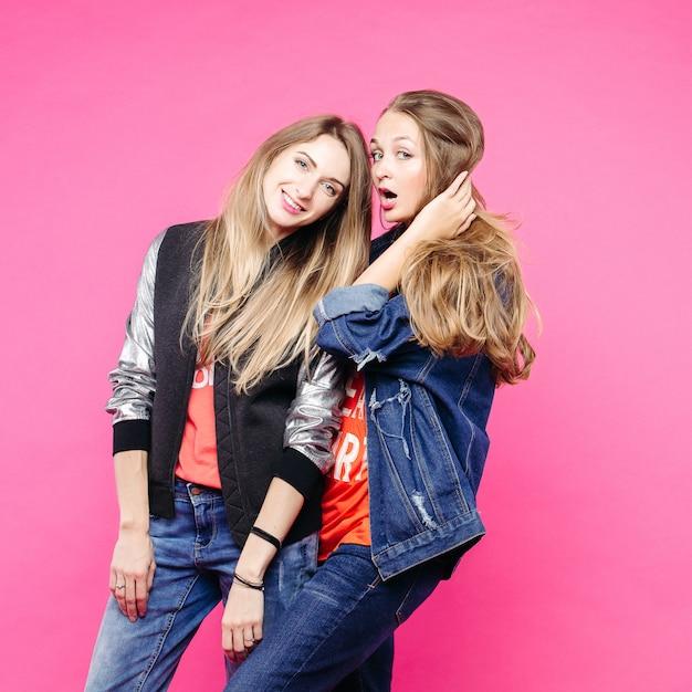 Beste vriendinnen dragen in een stijlvolle jeans-outfit bij roze.
