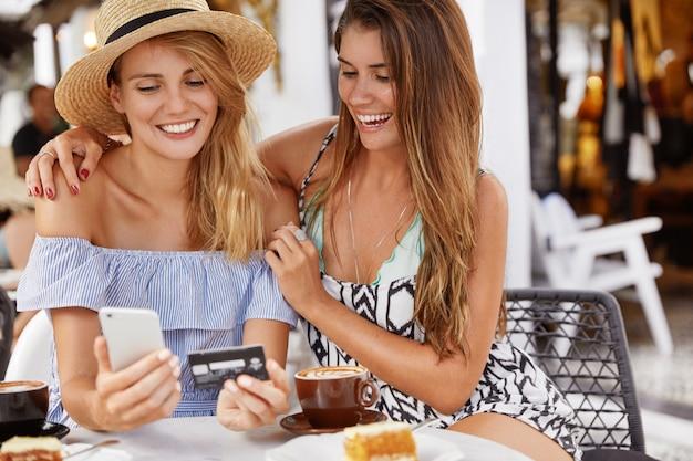 Beste vriendinnen vrouwen ontmoeten elkaar in cafetaria, blij om online te winkelen met smartphone en plastic kaart