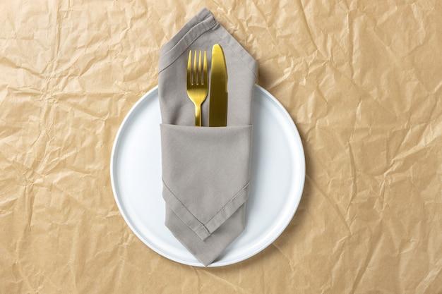 Bestek, gouden vork en mes in gevouwen stoffen servet op witte ronde plaat op verfrommeld kraftpapier, minimale stijl plat leggen, kopie ruimte.