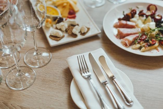 Bestek, hapjes en wijnglazen op de houten tafel in het restaurant.