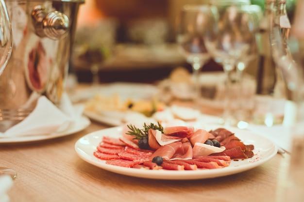 Bestek, hapjes, kwispedoor en glazen op de houten tafel in het restaurant