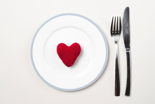 Bestek in de buurt van bord met hart