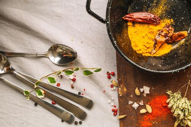 Bestek in de buurt van pan met kruiden