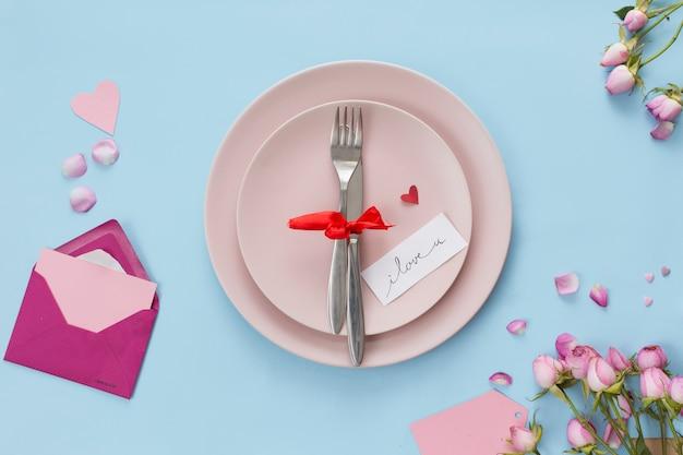 Bestek op platen tussen envelop en bloemen