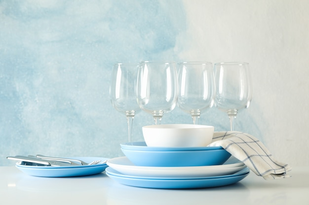 Bestek prachtig gestapeld op witte tafel tegen blauwe tafel