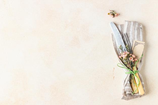 Bestekset en mooie roze bloemen op lichte stenen tafel