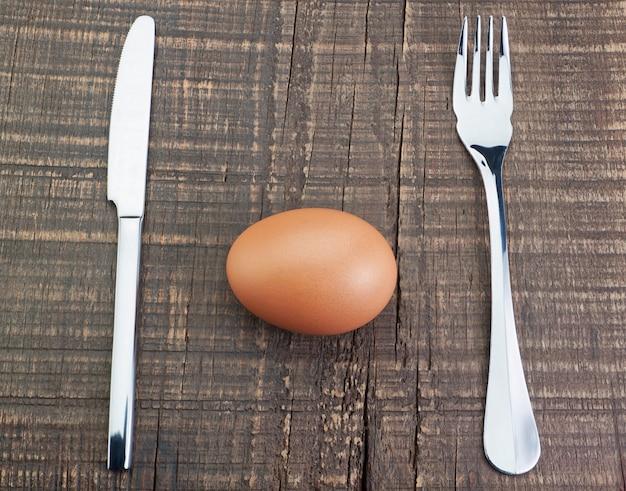 Bestekvork en mes en ei. op een houten structuur.