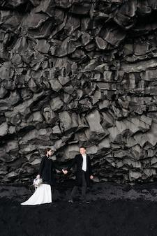Bestemming ijsland bruidspaar onder een rots van basaltstenen bruid en bruidegom op de