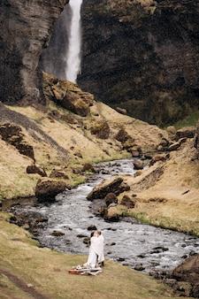 Bestemming ijsland bruiloft bij kvernufoss waterval een bruidspaar staat onder een plaid bij een