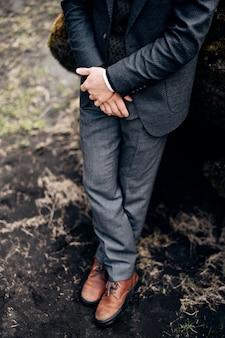 Bestemming ijsland bruiloft close-up van mannelijke benen in grijze broek en lederen bruine schoenen