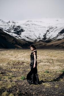 Bestemming ijsland bruiloft een bruid in een zwarte jurk met een zich ontwikkelende trein