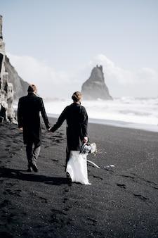 Bestemming ijsland bruiloft een bruidspaar loopt langs het zwarte zandstrand van vik in de buurt van de