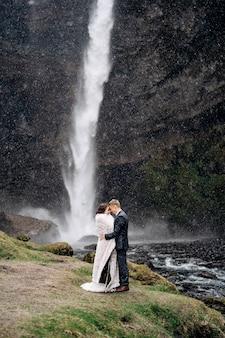 Bestemming ijsland bruiloft in de buurt van de waterval van kvernufoss het bruidspaar staat in de buurt van de waterval