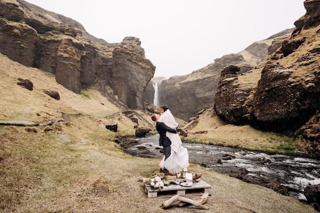 Bestemming ijsland bruiloft in de buurt van kvernufoss waterval bruidspaar aan de oever van een berg