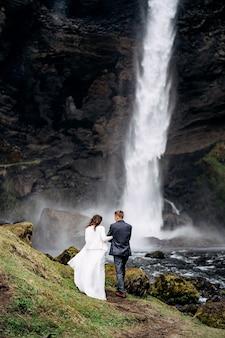 Bestemming ijsland bruiloft in de buurt van kvernufoss waterval bruidspaar gaat naar de waterval
