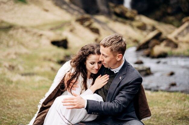 Bestemming ijsland bruiloft, nabij kvernufoss waterval. een bruidspaar zit aan de oevers van een