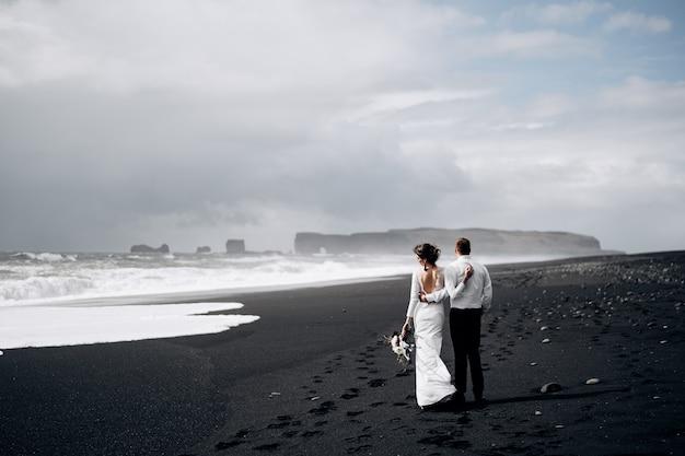 Bestemming ijsland trouwen een bruidspaar loopt langs het zwarte strand van vic sandy beach